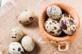 Raw quail eggs in a wooden bowl on burlap background — Stock Photo