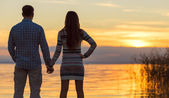 Couple holding hands at the lake — Stock Photo