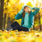 Woman sitting on  ground in autumn park. — Stock Photo