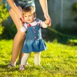 Baby girl is doing her first steps with mothers help — Stock Photo #61544005