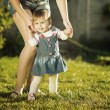 Baby girl is doing her first steps with mothers help — Stock Photo #61544199