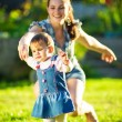 Baby girl is doing her first steps with mothers help — Stock Photo #61544371