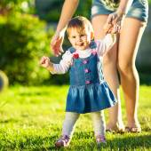 Baby girl is doing her first steps with mothers help — Stock Photo