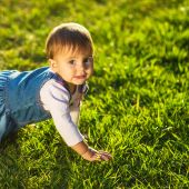 Baby-girl crawling at the green lawn. — ストック写真