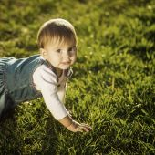 Baby-girl crawling at the green lawn. — Foto de Stock