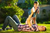 Father and baby daughter having fun in sunny garden. — Stockfoto