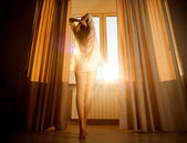 Woman  looking at sunrise standing near window — Foto Stock