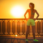 Fitness woman watching sunrise on quay — Stock Photo