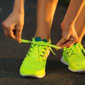 Woman tying laces on running shoes — Stock Photo