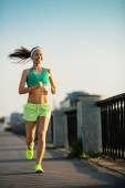 Woman running in city on quay — Zdjęcie stockowe