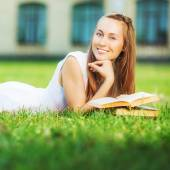 Student woman with book lying on lawn — ストック写真