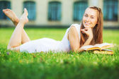 Student woman with book lying on lawn — Stockfoto