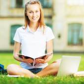 Student woman sitting on lawn — Stockfoto