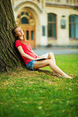 Student woman dreaming near tree with book — Stock Photo