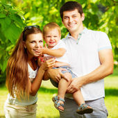 Young family having fun in  summer park — Stockfoto