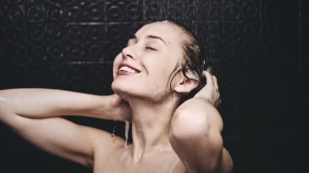 Woman rinsing hair from shampoo — Vídeo de stock