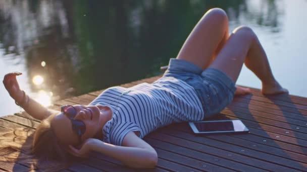 Mujer relajante en el embarcadero de madera — Vídeo de stock
