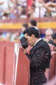 Bullfighter with montera starting rite of praying before bullfig — Stock Photo