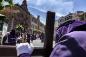 Penitent praying on his cross in front of church during Holy week — Foto de Stock