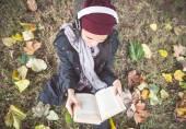 Girl reading book in a garden — Stock Photo