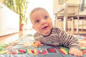 Baby with blue eyes playing at home — Stock Photo