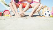 Three friends sitting on a beach deck — Stock Photo