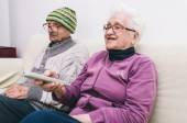 Old couple watching television — Stock Photo