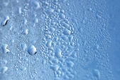 Blue abstract background with drops on glass surface — Stock Photo