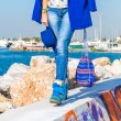Outdoor fashion portrait of beautiful model, wearing warm stylish outfit with coat and sneakers in city yacht club. Autumn street style. — Stock Photo #65147255