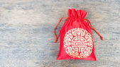 Red silky money bag on wood desk — Stok fotoğraf