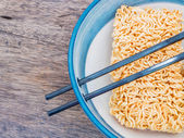 Instant noodles in bowl with chopsticks — Stock Photo