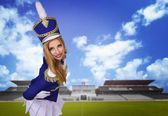 Beautiful blonde cheerleader drummer majorette  on the playground with green grass — Stock Photo