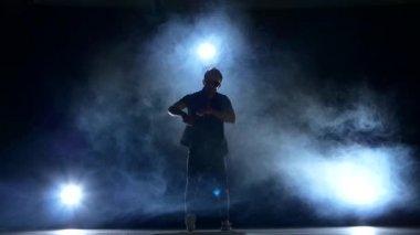 One hip hop break-dancer stylish man in sunglasses starts  dancing, smoke, silhouette, slow motion — Stock Video