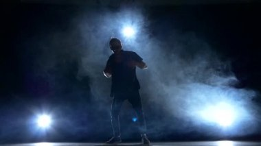 One hip hop break-dancer stylish man in sunglasses continue dancing, smoke, silhouette, slow motion — Stok video