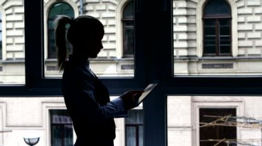 Girl in  lunch break reading book on your tablet standing at the window. Silhouette — Stock Video