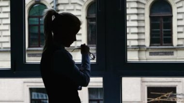 Businesswoman standing at the window after a busy day. Silhouette — Stockvideo