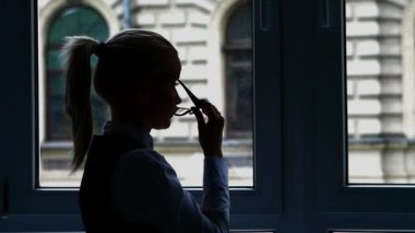 Silhouette Businesswoman standing at the window after a busy day. Slow motion — Stock Video