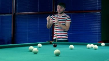 Young man lubricates cue chalk before impact — Stock video