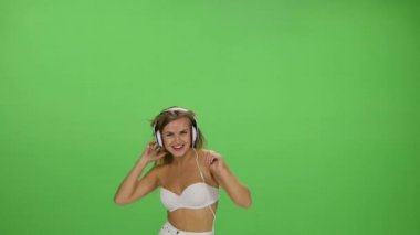 Young beautiful blonde girl dancing with headphones isolated on a green screen — Stok video