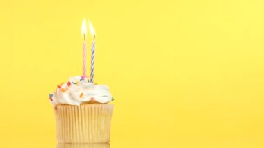 Smakelijke verjaardag cupcake met twee kaars, op gele achtergrond — Stockvideo