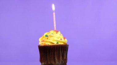 Smakelijke verjaardag cupcake met een kaars, op paarse achtergrond. — Stockvideo