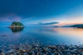 Small idyllic green isle at stoney coast in italy while sunrise — Foto de Stock