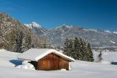 Snow landscape in austrian alps with wooden timber shed — Stock Photo