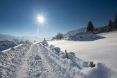 Tractor tracks in snow landscape at sunny winter day in tirol — Stock Photo