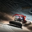 Night shot of red snow groomer at work in austria — Stock Photo #64015807