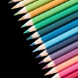 Many color pencils in a row on black background — Stock Photo #67644017