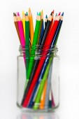 Glass full of sharpened wooden color pencils standing on white background — Stock Photo