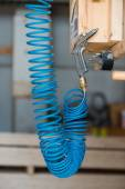 Blue compressed pneumatic air hose with pistol hanging at screw — Stock Photo
