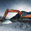 Big shovel excavator standing on gravel stones before lake — Stock Photo #70109145