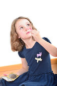 Little cute girl posing while panting her face — Stock Photo